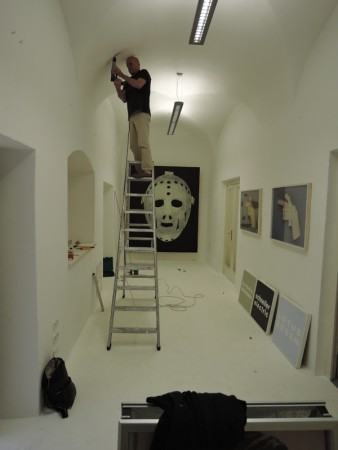 Viktor drilling a hole for hanging Klaus Scheuringer's pictures in the Project Space